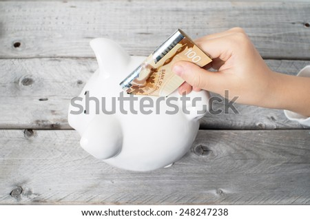 Asian boy hand inserting a hundred dollars bank note into white piggy bank  against wooden grey background - stock photo