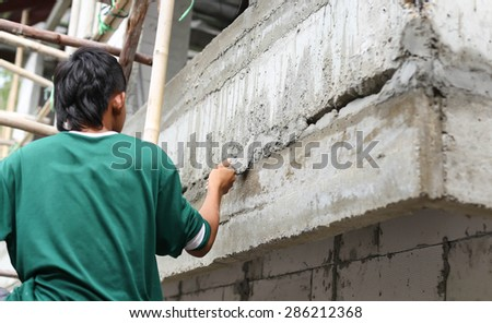 Asian boy hand using trowel with wet concrete wall in Thailand - stock photo