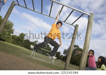 Asian boy hanging on jungle gym - stock photo