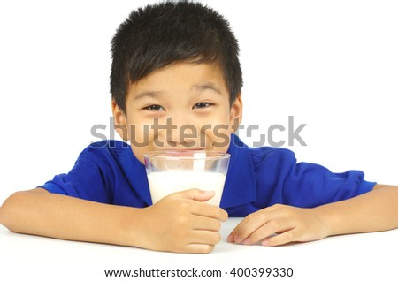 asian boy happy drinkking and holding glass of milk - stock photo