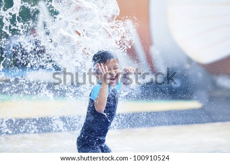 Asian boy having fun with pool fountain shot during summer time - stock photo