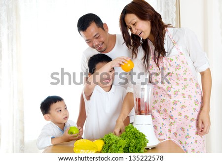 Asian boy helping mother in the kitchen - stock photo