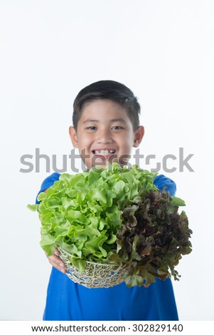 Asian  boy hold vegetables salad in basket/shallow depth of field - stock photo