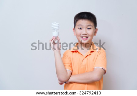 Asian boy holding a lamp, energy saving lamp, on grey wall background with soft shadow - stock photo