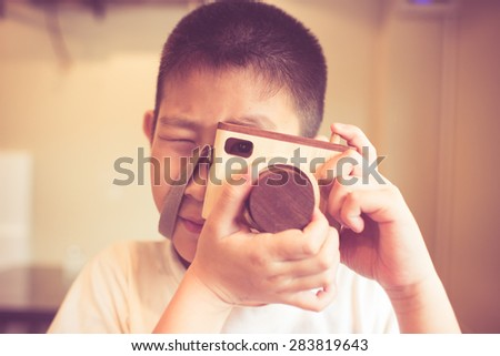 Asian boy holding a wooden camera toy.