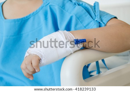 Asian boy ill in hospital with Blue pajamas bandage hand