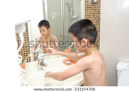 Asian boy in bathroom ready to wash himself, take photo by mirror reflection. - stock photo