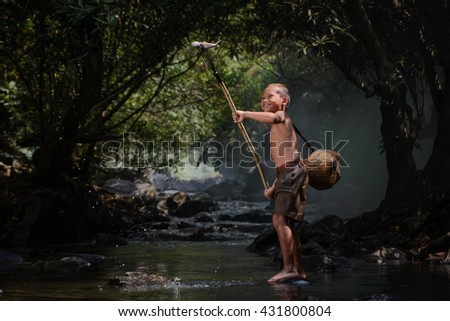 Asian boy is fishing at waterfall with fog and big tree background, boy smiling and very happy.