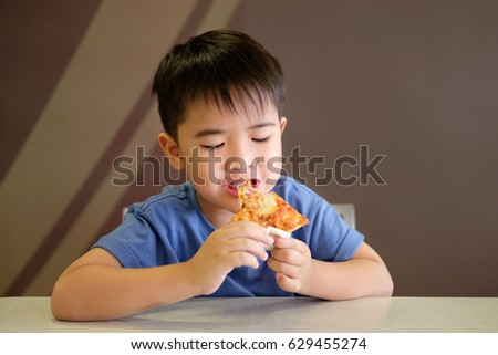 Asian boy is happy to eat pizza on brown background.