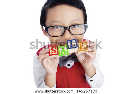 Asian boy is holding SALE wooden alphabet toy, isolated on white