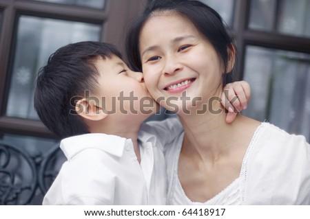 asian boy kissing his mum - stock photo