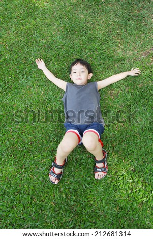 Asian boy  laying on the green grass field