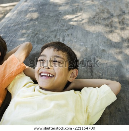 Asian boy laying with arms behind head - stock photo