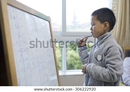 Asian boy learning caculation on white board in classroom - stock photo