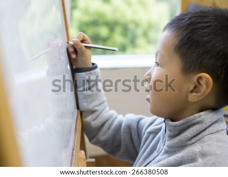 Asian boy learning Calculation on white board in classroom - stock photo