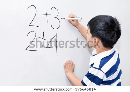 Asian boy learning calculation on white board in classroom. - stock photo