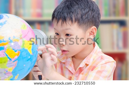 Asian boy looking at a globe in library  - stock photo