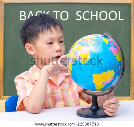 Asian boy looking at globe in classroom