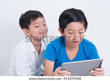asian boy play tablet mobile kid indoor digital technology using fun - stock photo