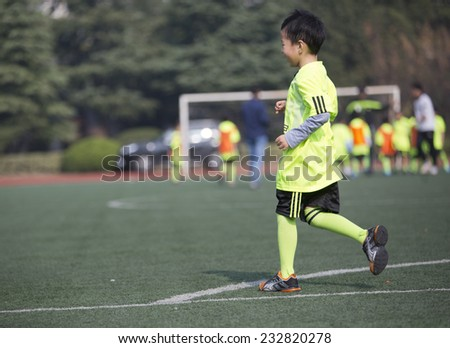 Asian boy playing football with happy