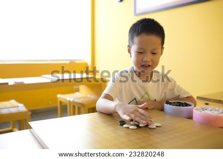 Asian boy playing  I-go in class