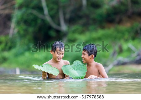 Asian Boy Playing in the river. Selective focus with shallow depth of field apply.
