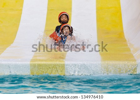 Asian boy playing in water park - stock photo