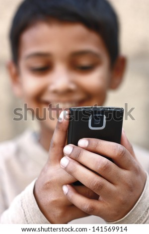 Asian boy playing on mobile phone - stock photo