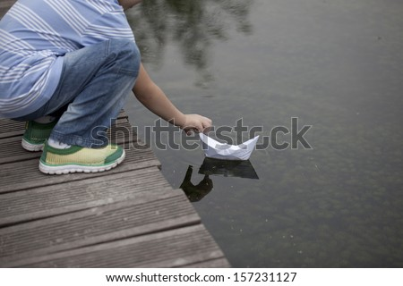 asian boy playing paper boat in lake