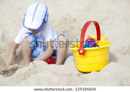 Asian boy playing sand on the beach in summer holiday