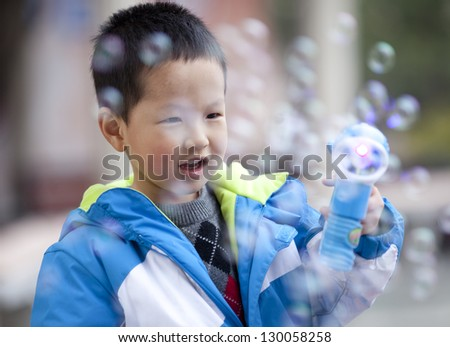 Asian boy playing soap bubble in the park