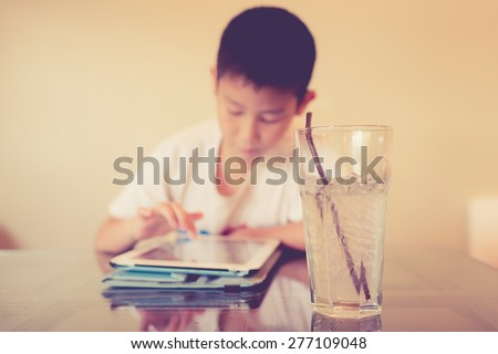 Asian boy playing table on table with cool drink. Selective focus at glass. - stock photo