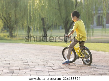 Asian boy riding bicycle at park in sunset,Shanghai - stock photo