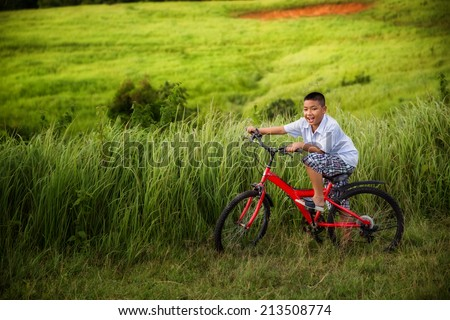 Asian boy riding on his bycicle in summer garden   - stock photo