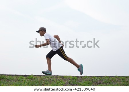 Asian boy running on the scenic road. - stock photo