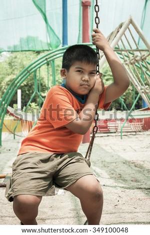 asian boy sad alone at playground - stock photo