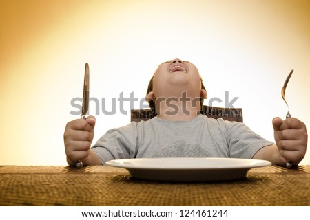asian boy screaming on dining table waiting for food - stock photo