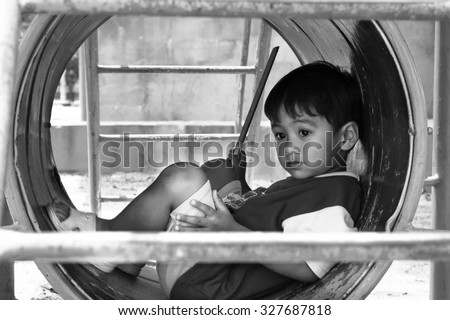 asian boy sitting alone at playground ,black and white tone - stock photo