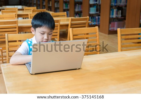 Asian boy sitting, he typing and browses the internet on a computer in library