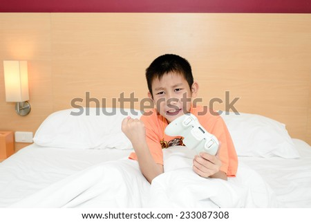 Asian boy sitting n bed playing video games - stock photo