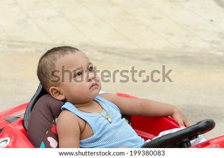 Asian boy sitting on a toy car.
