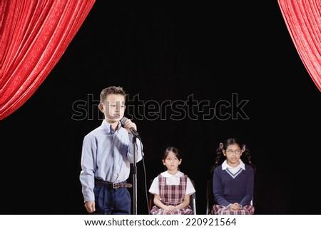 Asian boy speaking into microphone on stage - stock photo