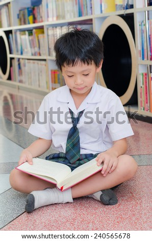 Asian boy student in uniform reading book in school library - stock photo
