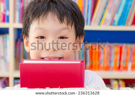 Asian boy student reading book in school library  - stock photo