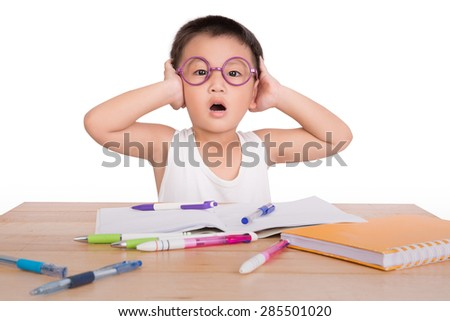 asian boy student serious to do homework at a table on a white background - stock photo