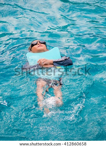 Asian boy swimming with the board in the pool