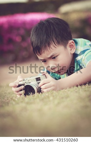 Asian boy taking photo by vintage film camera on blurred nature background at the day time. Adorable child enjoying at park. Outdoors. Retro picture style. - stock photo
