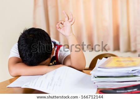 Asian boy tired of homework.but him OK - stock photo