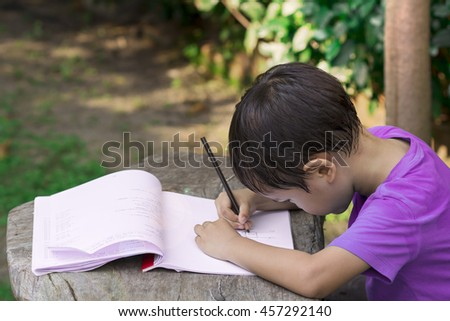 asian boy use pencil writing on notebook in the park - stock photo