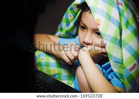 Asian boy using laptop for knowledge at night - stock photo